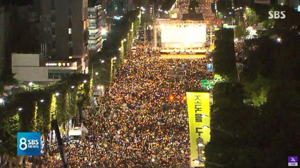 촛불집회 한 가운데서 펼쳐진 '조국을 구속하라'는 내용의 초대형 현수막. 사진=SBS뉴스 캡처.