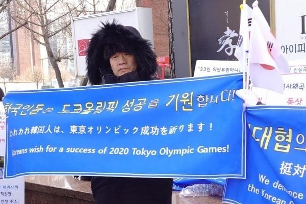 """""""한국인들은 도쿄올림픽 성공을 기원합니다!""""라는 내용의 현수막을 든 조희문 영화평론가."""