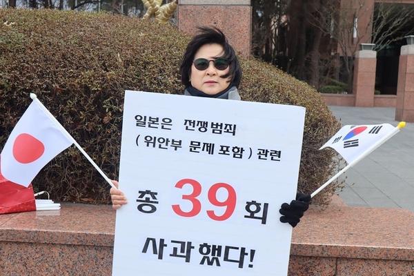 일본이 일찍이 39번이나 과거사 문제로 사과했음을 알리는 피켓을 든 이경자 전국학부모단체연합 대표.