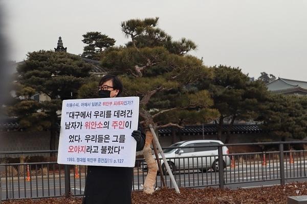 정대협의 위안부 증언집 내용이 담긴 피켓을 들고 침묵시위를 하는 국민행동 이인규 대외협력단장