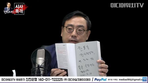 변 고문이 한동훈 검사장에게 줄 책 '변희재의 태블릿 사용설명서'에 사인한 뒤 들어보이는 모습.