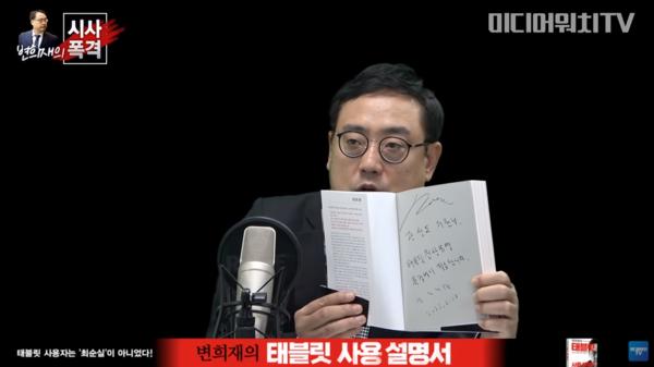시사폭격 방송에서 곽상도 의원에게 보낼 책을 들어보이는 변 고문.