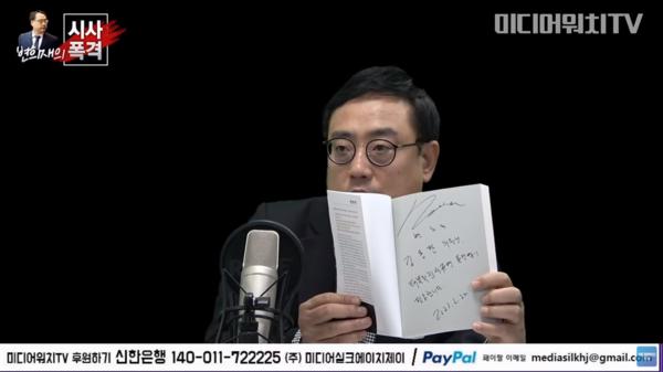 시사폭격 방송에서 김용판 의원에게 보낼 책을 들어보이는 변 고문.