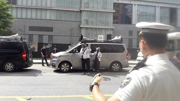 기자회견 장소 건너편에 주차한 차량에서 집회 참석자들이 발언하는 동안 큰 소리로 음악을 틀었다.