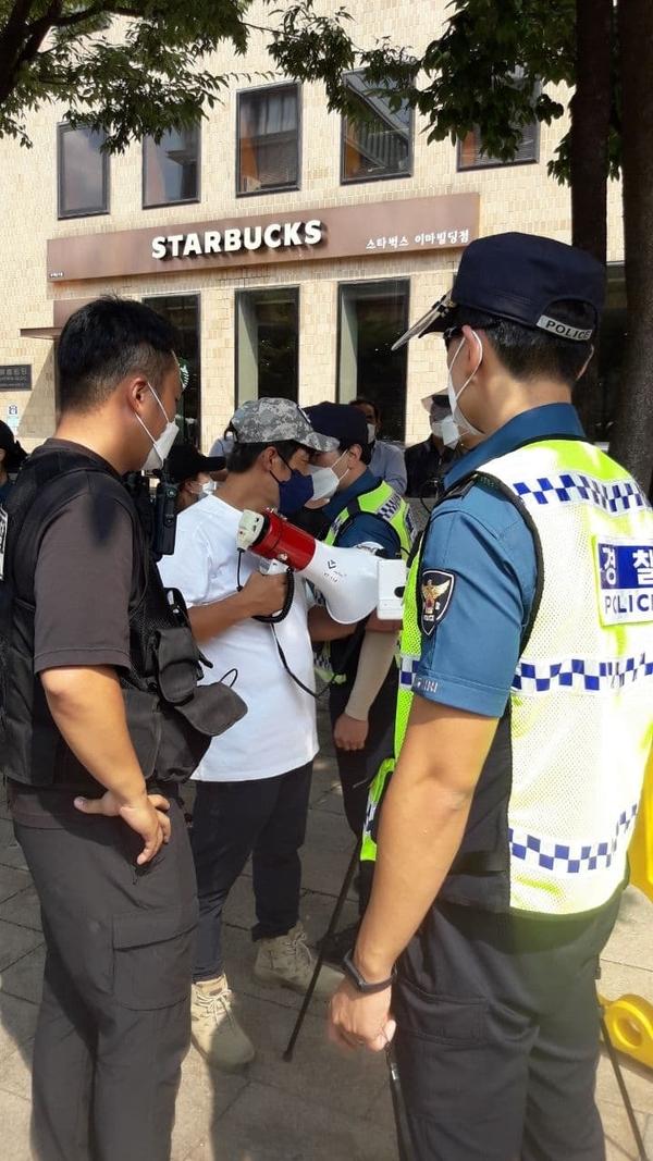 경찰이 확성기를 든 사람을 둘러싸고 있는 모습.